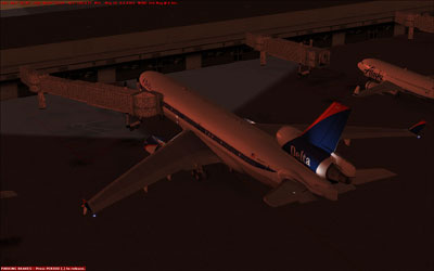 Delta MD-11 docked at gate at night