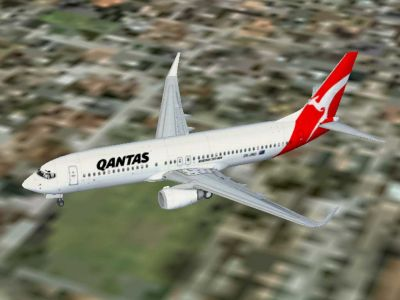 Qantas Jet Connect Boeing 737-800 flying over a city.