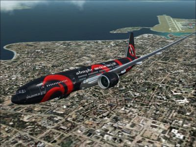 Team Alinghi Boeing 777-200 flying over a coastal city.