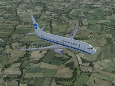 Xiamen Airlines Boeing 737-800 flying over countryside.