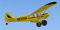 Screenshot of yellow Piper Super Cub N2355H in flight.