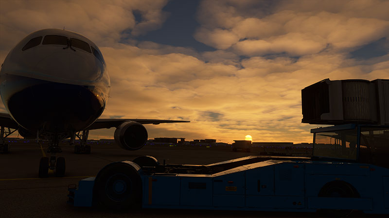 Boeing 787 on ramp preparing for early morning departure with sunrise in the background.