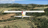 Screenshot of plane flying over St Rome de Tarn scenery.