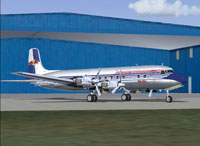 Screenshot of The Flying Bulls Douglas DC-6B oin the ground outside the hangar.
