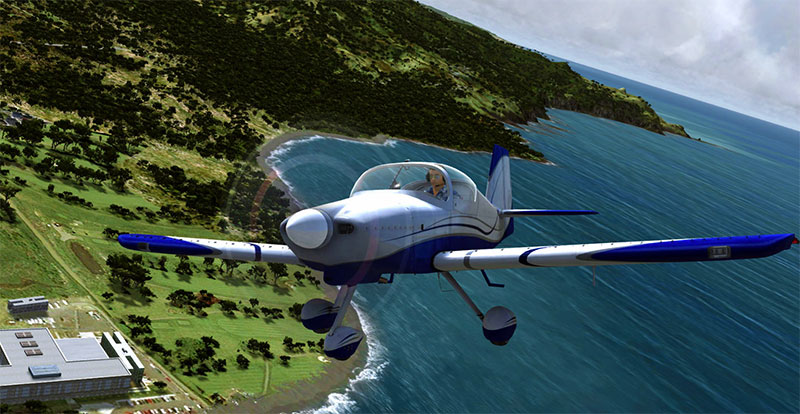 GA aircraft flying over coastline and water.