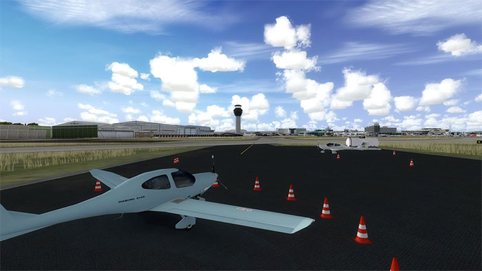 General aviation aircraft area with control tower in background.