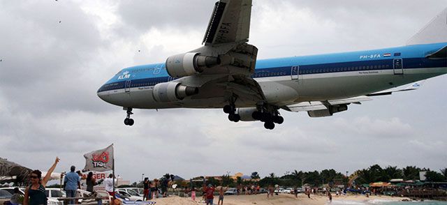 A KLM Boeing 747 landing over the beach.