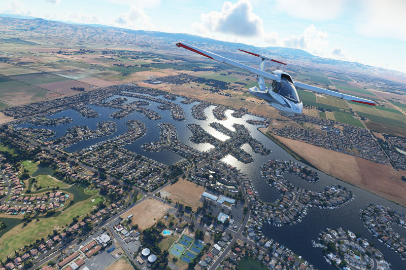 Icon A5 flying over terrain with lakes below and mountains in the distance.