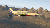 Piper M600 midflight above mountains.