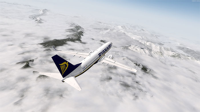 Ryanair 737 flying over mountains with clouds covering them.