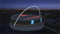Wembly stadium at night with lights.