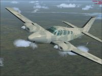 Camouflaged Beechcraft Baron in flight.