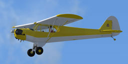 Basic yellow Piper J-3 Cub in flight.