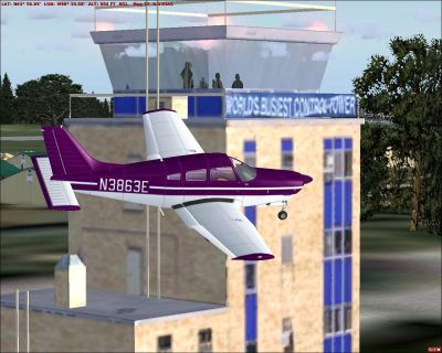 Purple Piper PA28R201 Arrow flying past control tower.