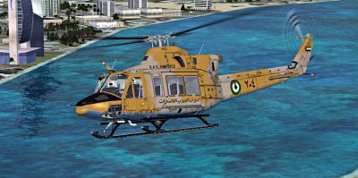 United Arab Emirates Air Force Bell 412 flying over water.