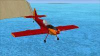Red and orange Zlin Z-50L in flight.