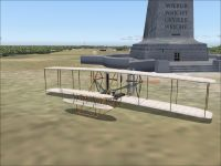 Screenshot of the Wright Flyer next to the Wright Memorial at Kitty Hawk in Microsoft Flight Simulator 2004.